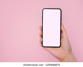 new technology and e-commerce concept from hand of business woman hold and show new smart phone on pink pastel background with copy space and clipping path