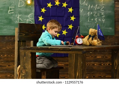 New technology. Little child use laptop computer in classroom with eu flag, new technology. New technology in elementary school. New technology for back to school. Tomorrow starts here.