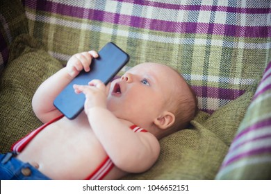 New technology, modern life. Infant use mobile phone or smartphone. Baby boy with suspenders lie in armchair. Child development concept. Childhood, infancy, innocence.