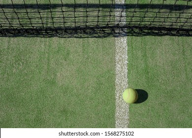 New tennis ball lies near the net. With copy space