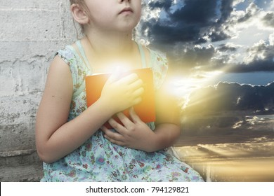 New Testament Psalms . Little girl is reading the Bible . spiritual education . the prayer book in the child's hands .  Religion background . sacred book