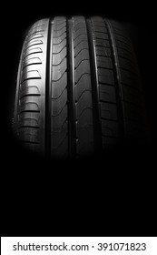 New  tire with modern tread on black background brightly lit from above.