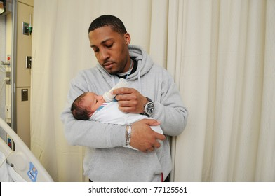 New Tired Family Father Holding Feeding Newborn Infant Baby in Hospital Room Just after Birth