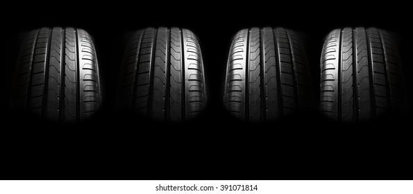 New  tires with modern tread on black background brightly lit from above.