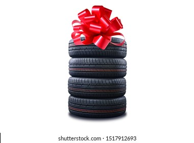 New tires pile as a gift  isolated on white. Tyres pile with a big red bow, as a present or bonus for buying a car.