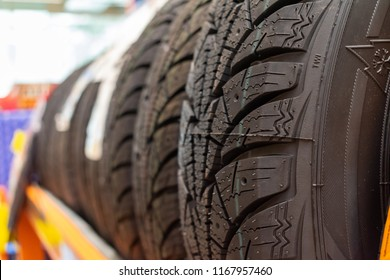 New tires for sale at booth in store. Stack of snow tyres. Winter tires.