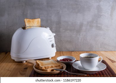 New toasted breads from the toaster  being served with jam and a cup of coffee on the wooden table for breakfast