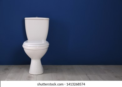 New toilet bowl near color wall indoors. Space for text