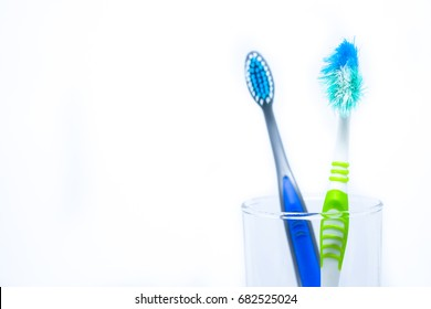"New toothbrush and old toothbrush (damaged) in clear glass for teeth cleaning isolated on white background - concept ""How often should you change your toothbrush ? """