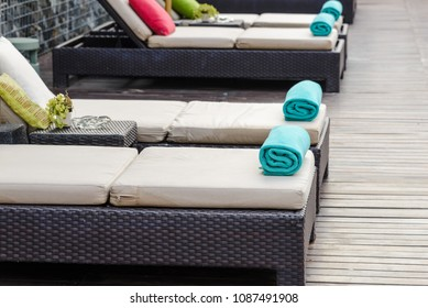 New towels on a sun-bed near a swimming pool.