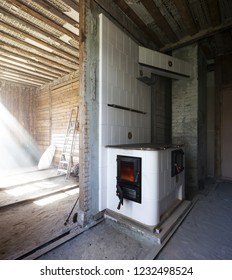 New traditional wood-burning stove of glazed white tiles in old unrenovated apartment. First heating fills room with smoke. Photographed in Estonia, Europe