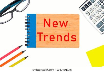 NEW TRENDS text written on a notepad. New business trends. Latest and latest trends. Evaluation methods