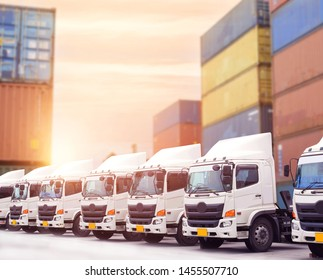 New truck delivery fleet with container depot yard and beautiful sky sunset.