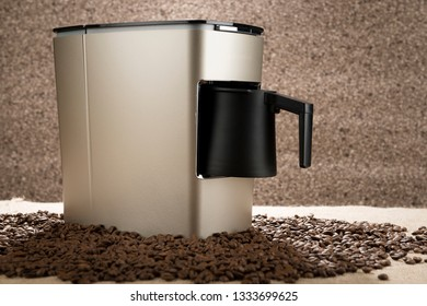 New Turkish coffee maker over coffee beans.