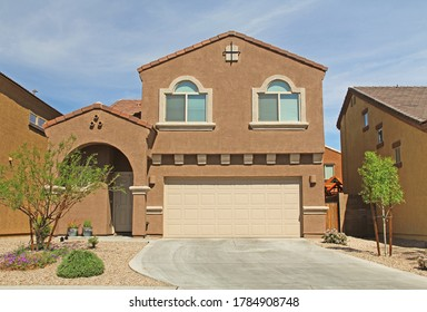New two-story, brown and beige stucco home in Tucson, Arizona, USA with beautiful blue sky and landscaping.