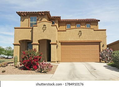 New two-story, brown and tan beige stucco home in Tucson, Arizona, USA with beautiful blue sky and landscaping.