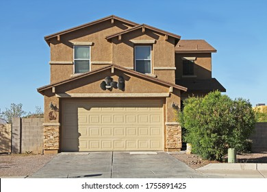 New two-story tan and brown stucco home in Tucson, Arizona, USA with beautiful blue sky and landscaping.