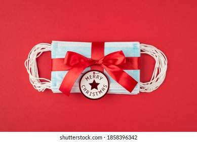 New type of giving presents concept. Top above overhead close up view photo of heap of disposable mask wrapped in red celebrating ribbon with tag isolated over bright cred color background