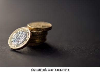 New uk one pound coins stack on dark background. British currency