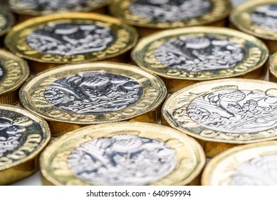 New UK One Pound Sterling Coins Laying Flat Closeup. British currency