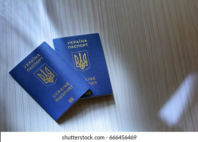 New ukrainian blue biometric passport with identification chip on wooden background with copy space.