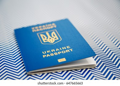 New ukrainian blue international biometric passport with identification chip on white and blue background. Selective focus.