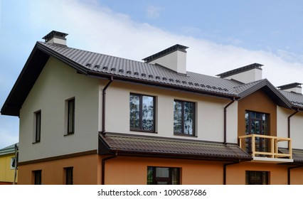 New unfinished cottage house with metal roof, rain gutter and balcony. Chimney and ventilation system