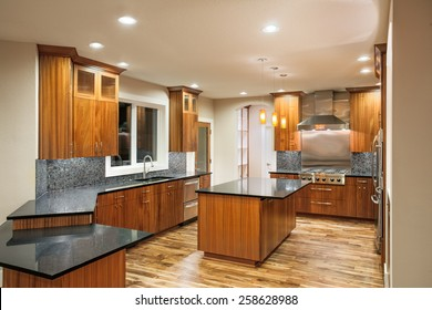 New Unfurnished Kitchen in Luxury Home with Island, Sink, Cabinets, and Hardwood Floors