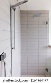 new upscale modern en suite bathroom with clean lines, white tile, brown cabinets