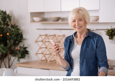 New user. Cheerful aged woman standing in the kitchen and using her smartphone while listening to music