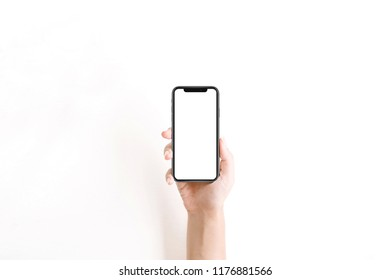 New version of smartphone iphon xs with blank screen in woman hand on white background. Flat lay, top view.