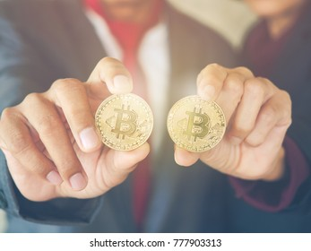 New Virtual currency of cryptocurrency or mining cryptography concept. Businessman and working woman with a suitcase holding gold bitcoin. Vintage tone and selective focus.