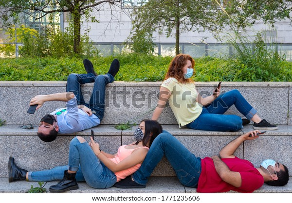 New way to socialize millennials in the city using protective masks, a group of young people committed to using their smartphones, sitting creatively on the steps in the city, focus on the red girl