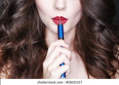 New ways for old habits. Cropped studio shot of an adorable red lipped model smoking electronic cigarette against black background.