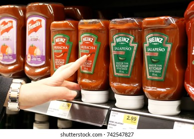 New Westminster, BC, Canada - April 15, 2017 : Close up woman buying Heniz ketchup hot pepper sauce inside buy low foods store