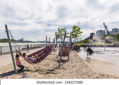 NEW WESTMINSTER, BC / CANADA – JULY 8, 2018: Families play in the playground and cool off in the spray from the splash pad.