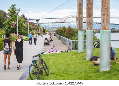NEW WESTMINSTER, BC / CANADA – JULY 8, 2018: People enjoy walking along the waterfront of the New Westminster Pier Park, with views of the Port Mann Bridge in the background.