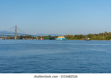 """New Westminster, BC/Canada - 8/3/2019: A Tugboat pulling a Ledcor Group barge in New Westminster, British Columbia, Canada looking from the Quay in the Fraser River, Skytrain Bridge into Surrey."""