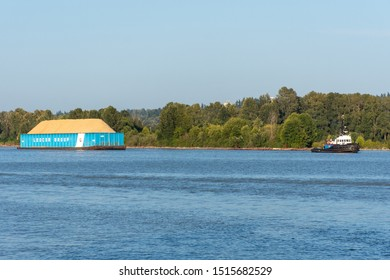 """New Westminster, BC/Canada - 8/3/2019: A Tugboat pulling a Ledcor Group barge in New Westminster, British Columbia, Canada looking into Surrey."""