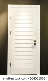 New White Closed Door with Frame, beautifully illuminated, built-in brown wall.
