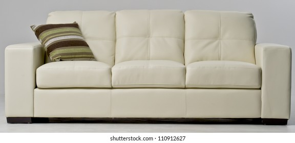 New white leather couch isolated on white with a green, brown and cream cushion