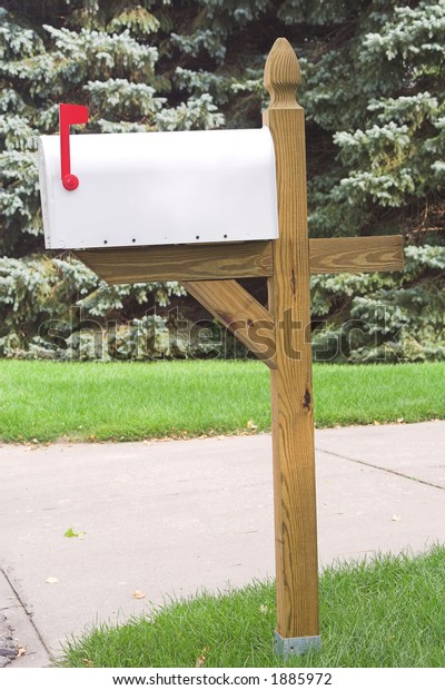 New white mialbox with red flag installed on wooden post and evergreens in background.  Ready for copy and graphics.