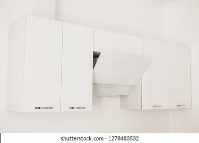 New white modern cupboard with hood. Furniture in the kitchen. Contemporary wooden cupboard. Ventilation hood