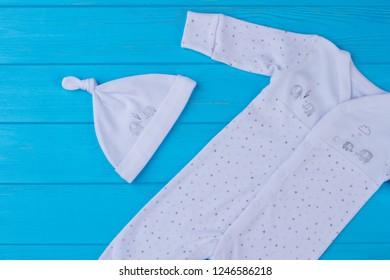 New white newborn pajama sleepwear and knot hat. Top view. Blue wood background.