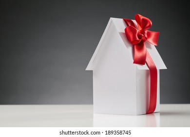 A new white paper house with a red ribbon on it - buying a new home concept.