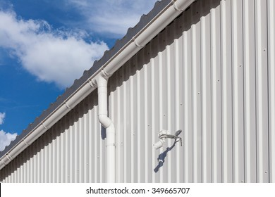 New white rain gutter on a building with white metal sheet and guard camera against blue sky