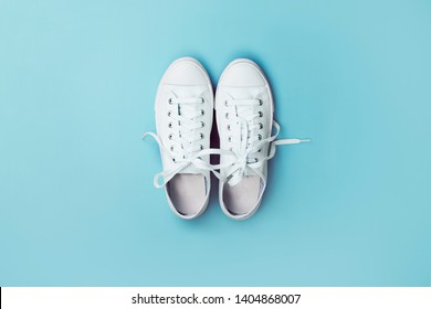 New white sneakers on blue background with copy space