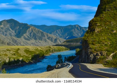 A new winding asphalt black road with a yellow dividing strip between the rocks and the Katun River in the Altai mountains under a clear blue sky with clouds and a field covered with green grass