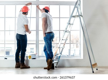 New windows, moving and repair in the apartment. Two workers make measurements of windows and repairs in a new apartment while ladder stands in an empty apartment.