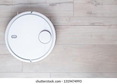 New wireless robot vacuum cleaner on clean floor. Top view. Copy space on wooden floor background.